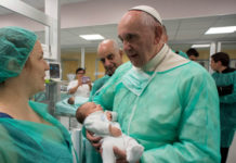 Pope Francis holds an infant at the neonatal unit as he visits the San Giovanni hospital in Rome, September 16, 2016.