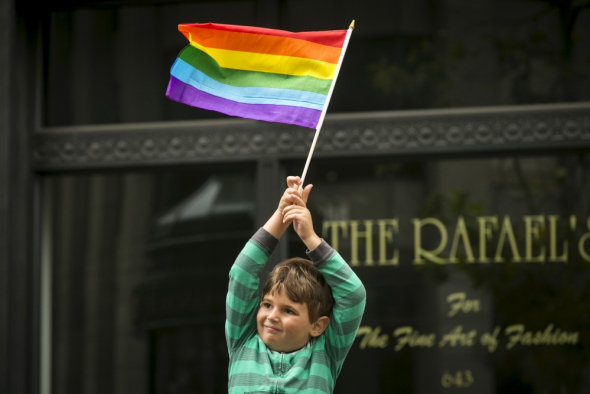 A young boy waves a rainbow flag while watching the San Francisco gay pride parade two days after the U.S. Supreme Court's landmark decision that legalized same-sex marriage throughout the country in San Francisco, California, June 28, 2015.
