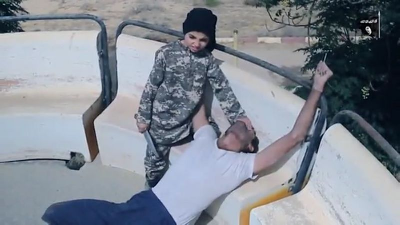 An ISIS child soldier is filmed holding a large knife while he stands over a victim in Syria in a video released in January 2017.